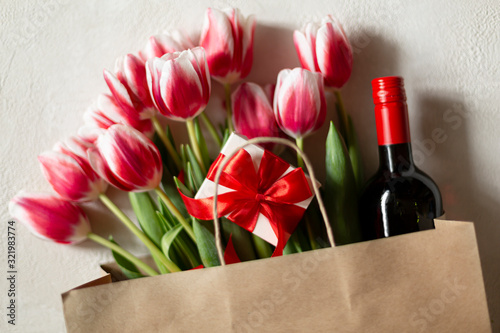 St. Valentine or Mother's Day. Beautiful red tulips, red ribbon, gift and a bottle of wine on light background. Day of birth. Greeting card.