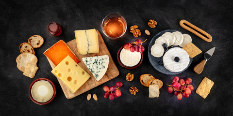 Cheese variety panorama with wine and fruit, a flat lay, overhead shot on a black background
