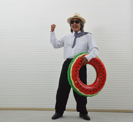 Happy funny elderly asian businessman in white shirt, sunglasses and straw hat holding watermelon inflatable ring standing over white wall, Business summer holiday concept