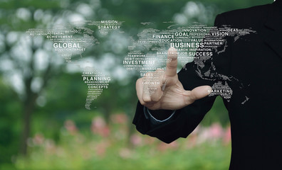 Businessman pressing global business words world map over blur flower and tree in park, Global business concept, Elements of this image furnished by NASA