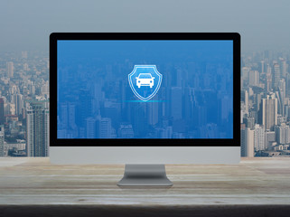 Car with shield flat icon on desktop modern computer monitor screen on wooden table over office building tower and skyscraper in city, Business automobile insurance online concept