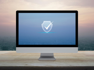 Security shield with check mark icon on desktop modern computer monitor screen on wooden table over city tower and skyscraper at sunset sky, vintage style, Technology internet cyber security and anti