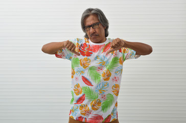 Upset elderly traveler asian man wearing summer shirt and glasses with thumb down sign standing over white wall, Negative facial expression, Business summer holiday concept