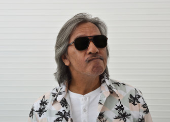 Portrait of happy senior traveler asian man wearing sunglasses and summer shirt over white wall background, Funny face expression pose, Business summer holiday concept