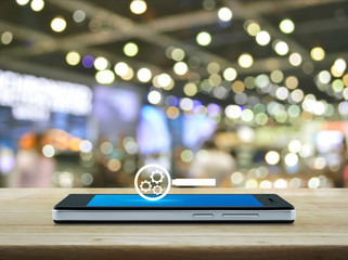 seo flat icon on modern smart phone screen on wooden table over blur light and shadow of shopping mall, Search engine optimization concept