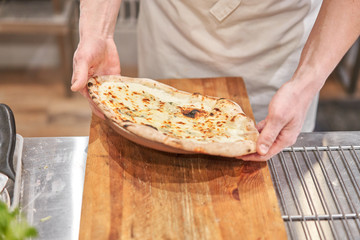 Italian kitchen and cooking concept. Chief with a pizza cutter cutting pizza to pieces at Neapolitan pizzeria.