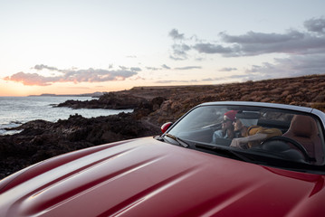 Couple driving convertible car, traveling near the ocean on a sunset, wide landscape view. Happy vacations and traveling by car concept