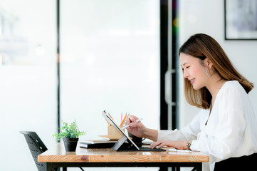 young businesswoman using digital pen writing on tablet screen while sitting at office desk in modern office, side view.