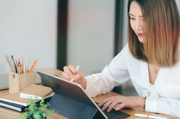 Shot of young businesswoman working with tablet while sitting at office desk in modern office.