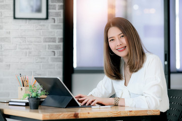 Young businesswoman working in modern office white happiness.