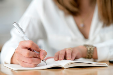 Close up view of woman hand using pen writing on notebook while sitting at wooden table. Copy space.