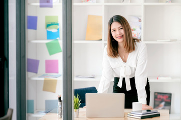 Portrait of beautiful businesswoman standing behind office desk with laptop.