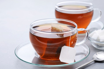 Cup of tea with tea bag on a gray background.