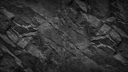 Deurstickers Stenen Black grunge background. Dark gray rock texture. Cracked rough stone surface. Mountain texture closeup. Black and white background. Volume. 3D effect.