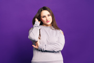 Plus size model in casual clothes, fat woman on purple background