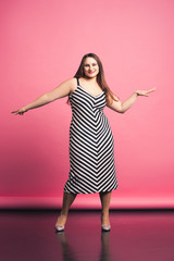 Happy plus size model in striped dress, fat woman dancing on pink background
