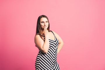Pensive plus size model in striped dress, fat woman on pink background