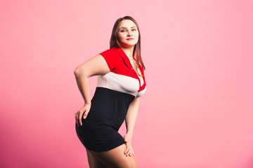 Sexy plus size fashion model in sports dress, attractive fat woman on pink background