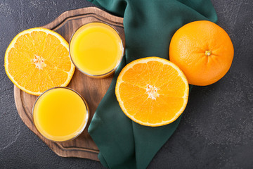 Glasses of fresh orange juice and fruit on dark background