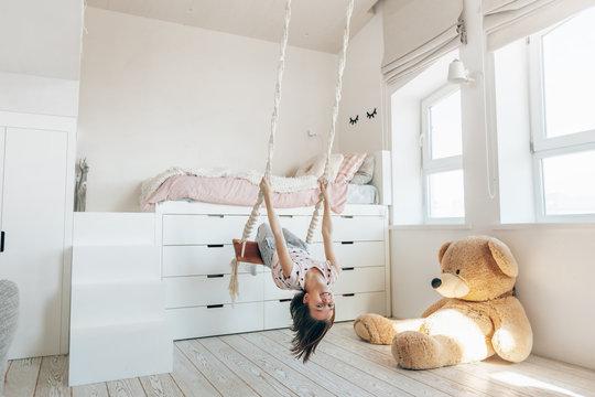 Child swinging in bright scandinavian playroom.