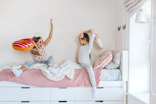Kids paljamas party in white bedroom interior