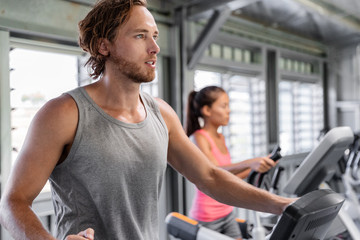 Fitness gym people training on elliptical cardio machine trainer. Interracial couple friends, Caucasian man, Asian woman working out together at gym health center.