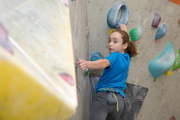 Boy on climbing wall, Bouldersport , boy climbing a rock wall indoor