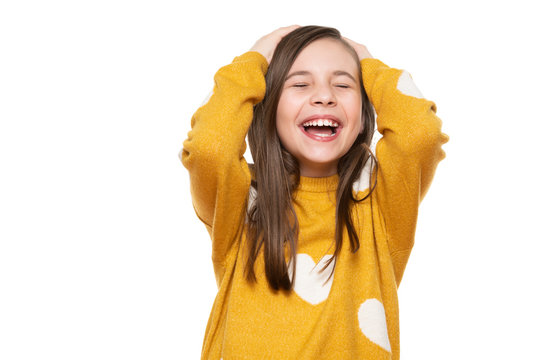 Waist up studio portrait of an adorable young girl laughing with excitement, head in hands and closed eyes, isolated on white backgroud. Human emotions and facial expressions concept.