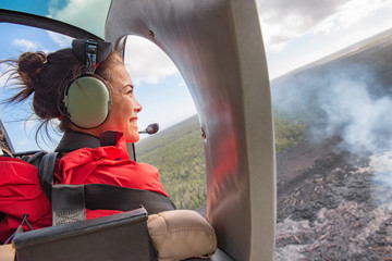 Helicopter doors off ride adventure travel Asian woman tourist happy looking at landscape of volcanic eruption above volcano fumes in Big Island, Hawaii. Fototapete