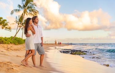 Wall Mural - Couple on romantic sunset beach walk relaxing during Hawaii summer travel vacation on Kauai island, USA. Asian woman in white dress, Man in linen shirt.
