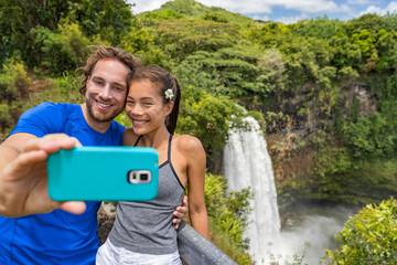 Hawaii couple tourists at Kauai waterfall taking selfie photo at famous landmark. Tourist destination Wailua Falls of Kauai island, Hawaii, USA hiking nature mountain vacation travel.