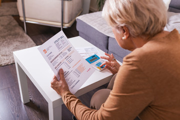 Senior woman with papers and calculator doing financial calculation at home.