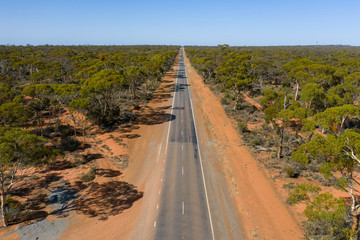 Aerial low angle view of a long straight road in the Australian outback in Western Australia