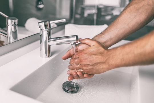 Washing hands rubbing with soap man for winter flu virus prevention, hygiene to stop spreading germs.