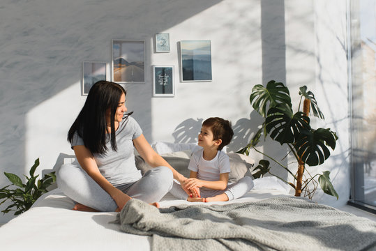 Beautiful pregnant woman and her cute little baby son are sitting in lotus position and smiling while meditating and doing yoga at home