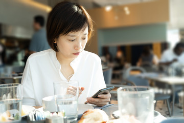 asian female using smart phone while have breakfast