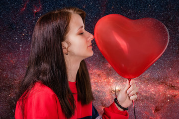 Girl among countless stars gently touches a big red heart-shaped balloon. Horoscope and Valentines Day concept. Elements of this image furnished by NASA