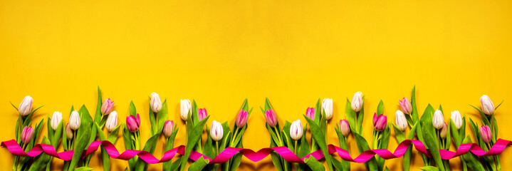 Colorful Banner Of Tulip Spring Flowers. Yellow And Pink Blossoms With Pink Ribbon. Yellow Wooden Background