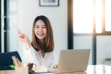 Portrait of young beautiful businesswoman holding pencil, smiling and looking at camera while sitting at office desk.