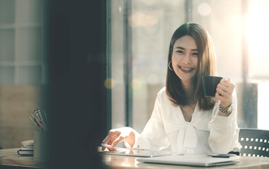 Portrait of young businesswoman holding cup, smiling and looking at camera while sitting at office desk.
