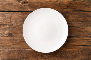 Overhead shot of empty white plate on rustic wooden table. Close up