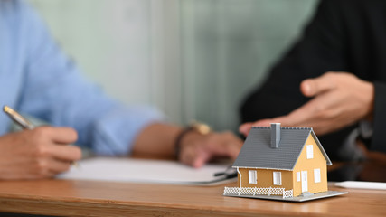 Fototapeta Cropped shot of Real estate agent offer house insurance or house ownership to smart man in blue shirt at the modern wooden table. Signing on agreement, Broker/Seller/Dealer concept. obraz