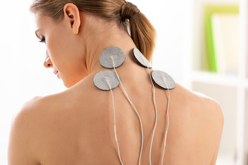 Back view of beautiful woman with electrodes on neck during electrotherapy in clinic