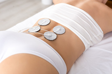Cropped view of stimulation electrodes on back of woman during electrotherapy in clinic