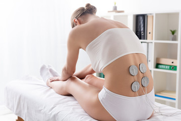 Back view of woman in underwear sitting on massage couch during electrode treatment of back in...