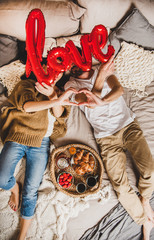Overhead view of young lovely happy caucasian couple in bed holding red inflated word love and having breakfast with croissants, top view. Saint Valentines day greeting card