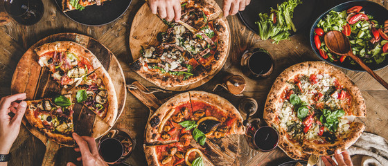Family or friends having pizza party dinner. Flat-lay of people eating various kinds of Italian pizza and drinking wine over wooden table, top view, wide composition. Fast food lunch concept