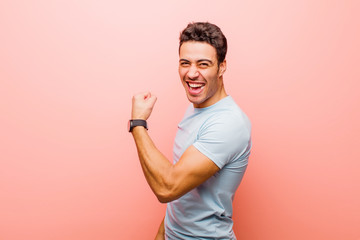 young arabian man feeling happy, satisfied and powerful, flexing fit and muscular biceps, looking...