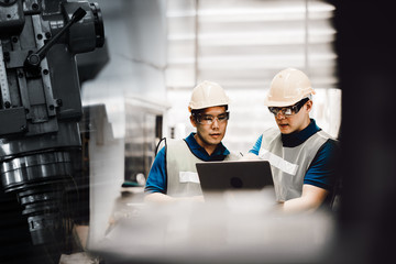 Two Asian workers in their 30s talking in a metal fabrication plant wearing hardhats and protective eyewear. The man pointing laptop and talking the new planning in modern factory.