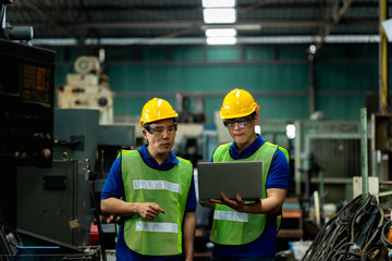 Mechanic and staff engineer talking nearby a machine in a big factory about latest new planing, Two men engineer talking in modern factory.